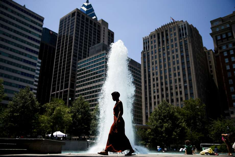 A woman walks past a fountain in John F. Kennedy Plaza, also known as Love Park, in Philadelphia during lunch time on Tuesday, June 24, 2014. (AP Photo/Matt Rourke) Photo: Matt Rourke, Associated Press