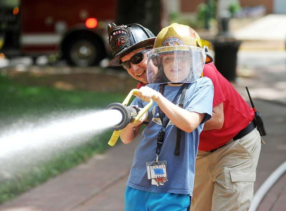 Elijah Hollis, right, a participant in a summer math camp at the University of Mississippi, operates a fire hose with Ethan Peterson as part of a lesson, Tuesday, June 24, 2014. in Oxford, Miss. (AP Photo/Oxford Eagle, Bruce Newman) MAGS OUT, NO SALES, MANDATORY CREDIT Photo: Bruce Newman, Associated Press