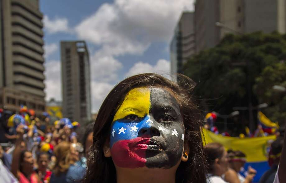 A woman with a representation of Venezuela's flag painted on her face attends an anti-government protest in Caracas, Venezuela, Tuesday, June 24, 2014. University students and government opponents marched in the east of the capital to protest the government of President Nicolas Maduro and demand the release of people who have been arrested in street demonstrations in recent months. (AP Photo/Ramon Espinosa) Photo: Ramon Espinosa, Associated Press