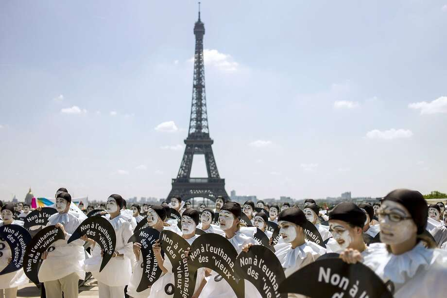 """TOPSHOTS People dressed as the traditionnal theatre character """"Pierrot"""" take part in a demonstration against euthanasia for elderly and dependent people on June 24, 2014 on the Trocadero esplanade, also called the Parvis of Human Rights, near the Eiffel Tower in Paris. Several hundred people took part in the demonstration taking place a few hours prior to a decision by the French Council of State on whether or not to stop the treatment keeping alive French tetraplegic patient Vincent Lambert, who is currently on artificial life support, and on the eve of a court decision in the trial of French doctor Nicolas Bonnemaison, accused of having poisoned 7 terminally ill patients in 2010 and 2011.  AFP PHOTO / FRED DUFOURFRED DUFOUR/AFP/Getty Images Photo: Fred Dufour, AFP/Getty Images"""
