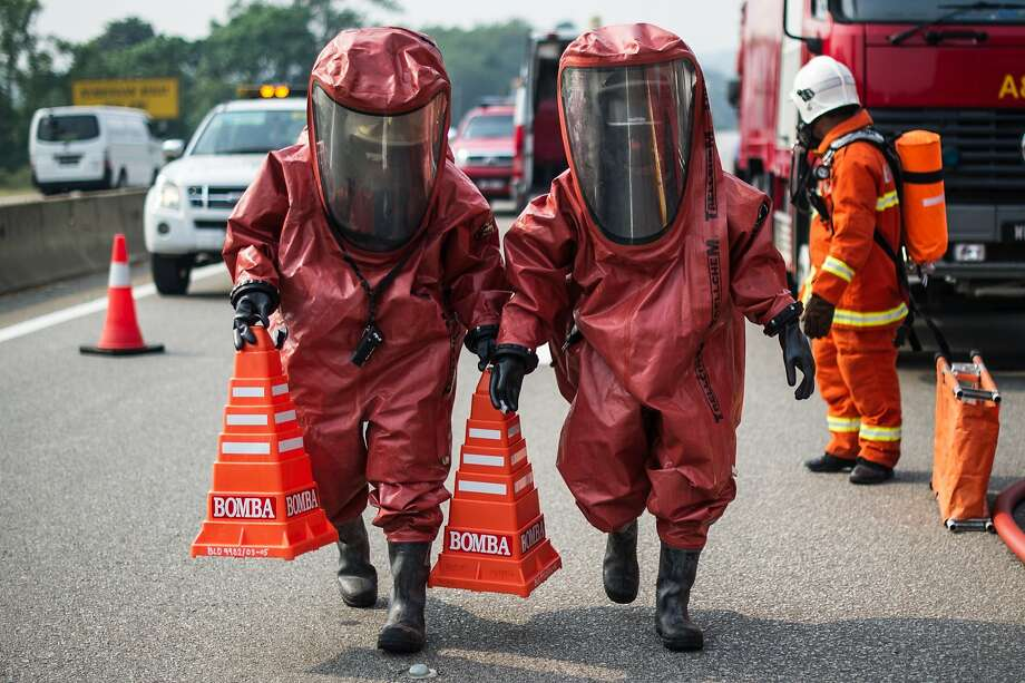 TOPSHOTS Members of a Malaysian hazardous disaster emergency response team wearing protective suits take part in a trasportation emergency response drill 'Ex-Eagle' on a highway near Bentong, outside Kuala Lumpur on June 24, 2014. The drill ensures transportation emergency incidents are managed in an effective and efficient manner. AFP PHOTO / MOHD RASFANMOHD RASFAN/AFP/Getty Images Photo: Mohd Rasfan, AFP/Getty Images