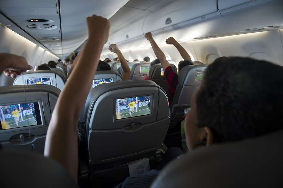 TOPSHOTS Brazilian football fans reacts to Neymar scoring against Cameroon as they watch the match live on TV in flight above the Amazonian jungle on June 23, 2014. The Azul flight from Manaus bound for Sao Paulo offered live streaming of the Brazil and Cameroon FIFA 2014 World Cup football match and the plane erupted in cheers when Brazil took an early lead.   AFP PHOTO / ODD ANDERSENODD ANDERSEN/AFP/Getty Images Photo: Odd Andersen, AFP/Getty Images