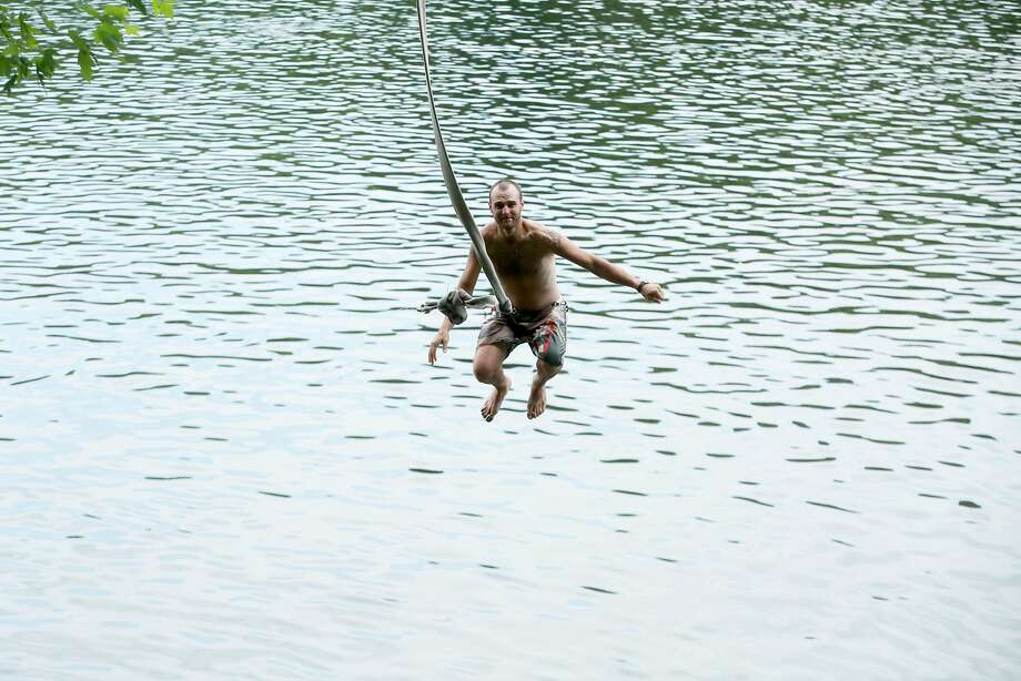 Nick Ginny, 30, Milford, N.J. swings out into a relatively warm Delaware River from a suspended fire hose Tuesday June 24, 2014.    ( AP Photo / The Philadelphia Inquirer, David Swanson )  PHIX OUT; TV OUT; MAGS OUT; NEWARK OUT Photo: Drs, Associated Press