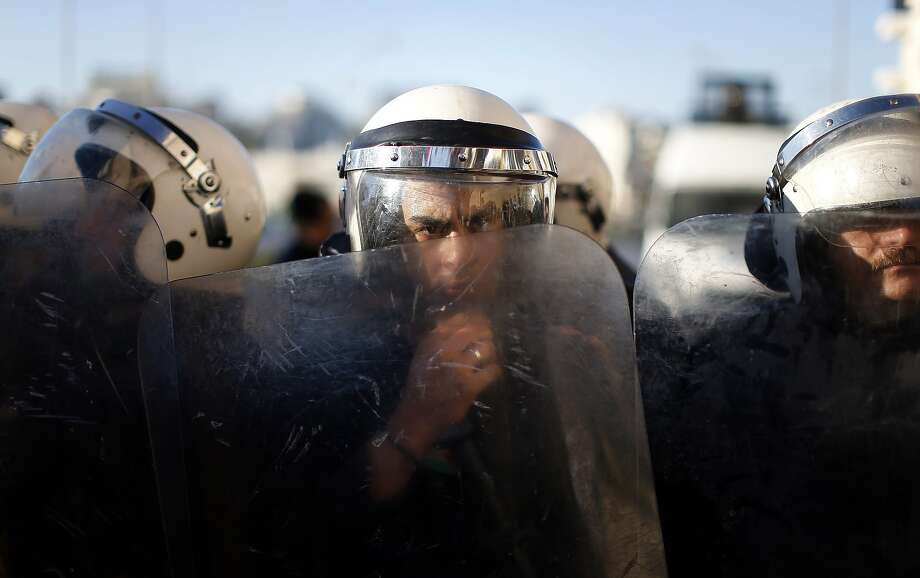 TOPSHOTS A Palestinian riot policeman looks on behind a shield as he, and his colleagues, blocks a street to Palestinian protesters who demonstrate against the new cooperation between the Palestinian police with the Israeli police to find three missing Israeli teenagers on June 23, 2014 in the center of the West Bank town of Ramallah. Since the youths disappeared from a hitchhiking stop in the southern West Bank on June 12, Israel has rounded up hundreds of Palestinians in a bid to find them, while also crushing the West Bank network of Islamist movement Hamas, which it accuses of abducting the teens.  AFP PHOTO / THOMAS COEXTHOMAS COEX/AFP/Getty Images Photo: Thomas Coex, AFP/Getty Images