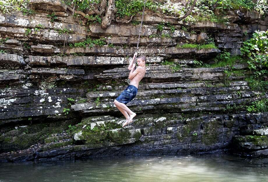 Michael Sheets, 13, of Criders swings into the water at the Blue Hole Picnic Area in Bergton, Va,  on Tuesday, June 24, 2014.   (AP Photo/Daily News-Record, Jason Lenhar) Photo: Jason Lenhar, Associated Press