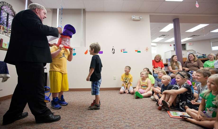 Jaymon Strickland, center, checks out Brett Woosley's head during Eldon Roark's illusion and comedy show at Carnegie Branch Library in St. Joseph, Mo., Tuesday, June 24, 2014. (AP Photo/The St. Joseph News-Press, Sait Serkan Gurbuz) Photo: Sait Serkan Gurbuz, Associated Press