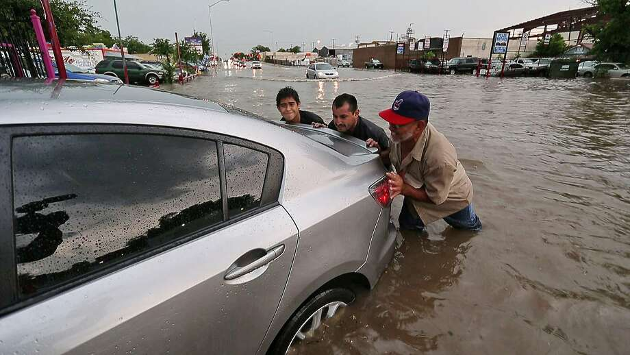 Jesus Papas, Delfino Moreno and Emilio Perales pitched in to push a car out of the high water in Hemphill Street in Fort Worth, Texas, Tuesday, June 24, 2014. (AP Photo/The Fort Worth Star-Telegram, Paul Moseley) Photo: Paul Moseley, Associated Press