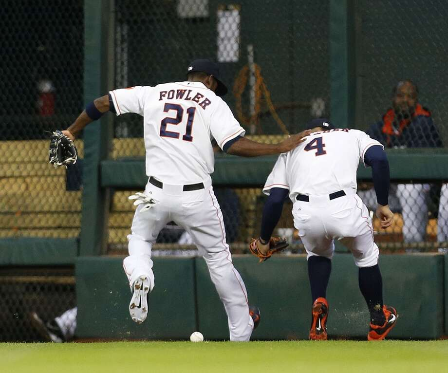 Astros center fielder Dexter Fowler (21) and George Springer (4) chase a double hit by Braves third baseman Chris Johnson (23). Photo: Karen Warren, Houston Chronicle