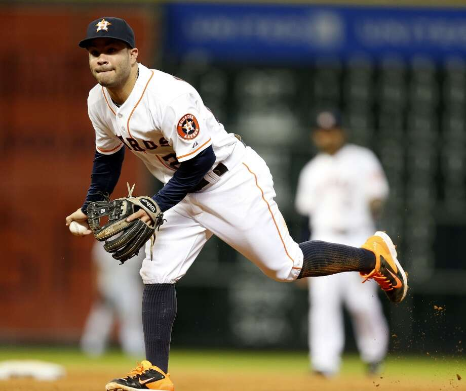 Astros second baseman Jose Altuve (27) makes the throw to first. Photo: Karen Warren, Houston Chronicle