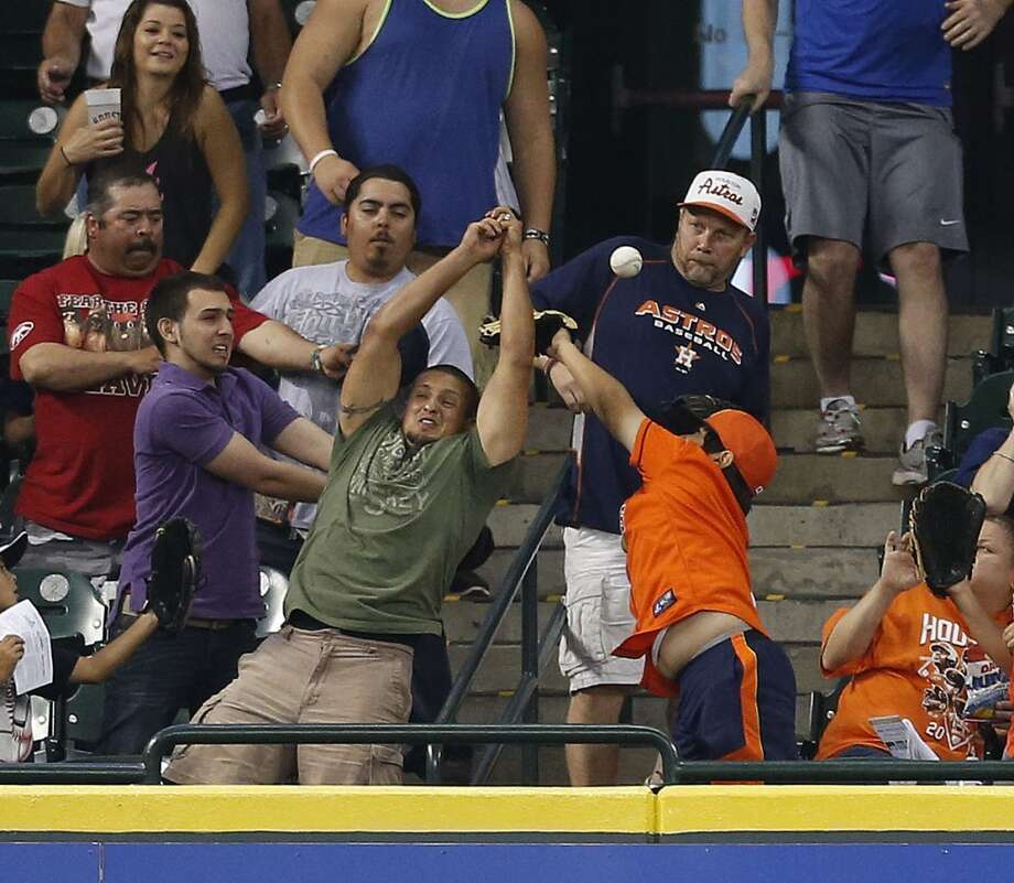 Fans in the Crawford Boxes reach for a home run ball hit by Braves center fielder B.J. Upton (2). Photo: Karen Warren, Houston Chronicle