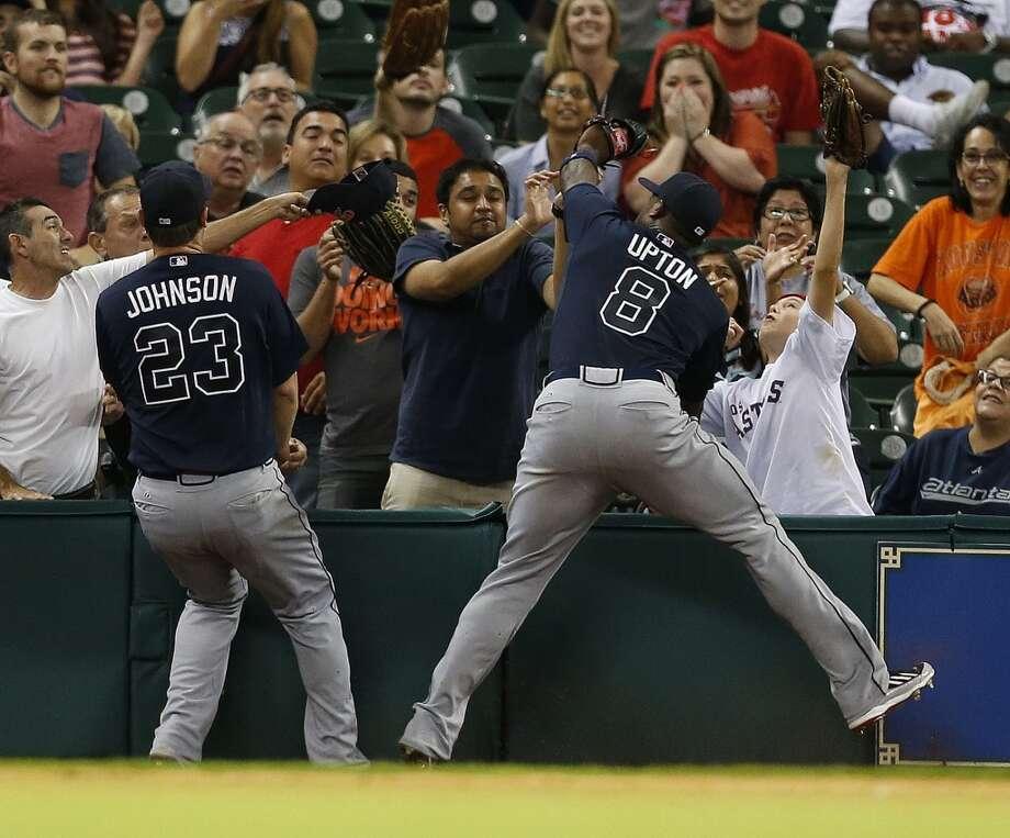 Braves third baseman Chris Johnson (23) and Justin Upton (8) both go for Jason Castro's fly out. Photo: Karen Warren, Houston Chronicle