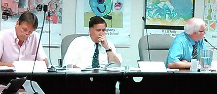 The Board of Education met in public session early Wednesday, after hours of closed-door discussion that began Tuesday night, to approve a raise and contract extension for Superintendent of Schools David Title, center. Title is flanked by board Vice Chairman Paul Fattibene, left, and Chairman Philip Dwyer. Photo: Andrew Brophy / Fairfield Citizen