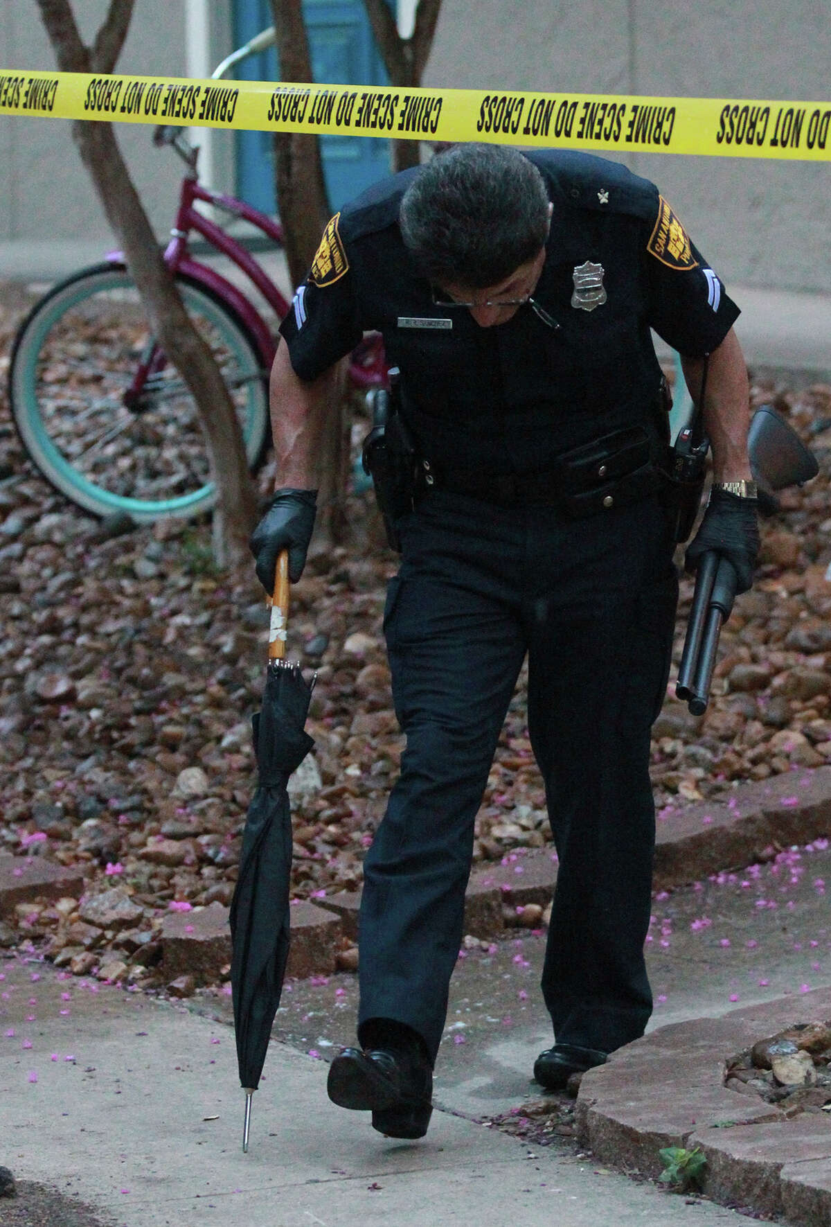 San Antonio police officer R.R. Sanchez walks to a patrol car Wednesday June 25, 2014 with a shotgun at the Avistar at Chase Hill apartments on the 15,800 block of Chase Hill where two men were shot. One man died at the apartment and another died at University Hospital according to San Antonio police sergeant Andrew Ling.
