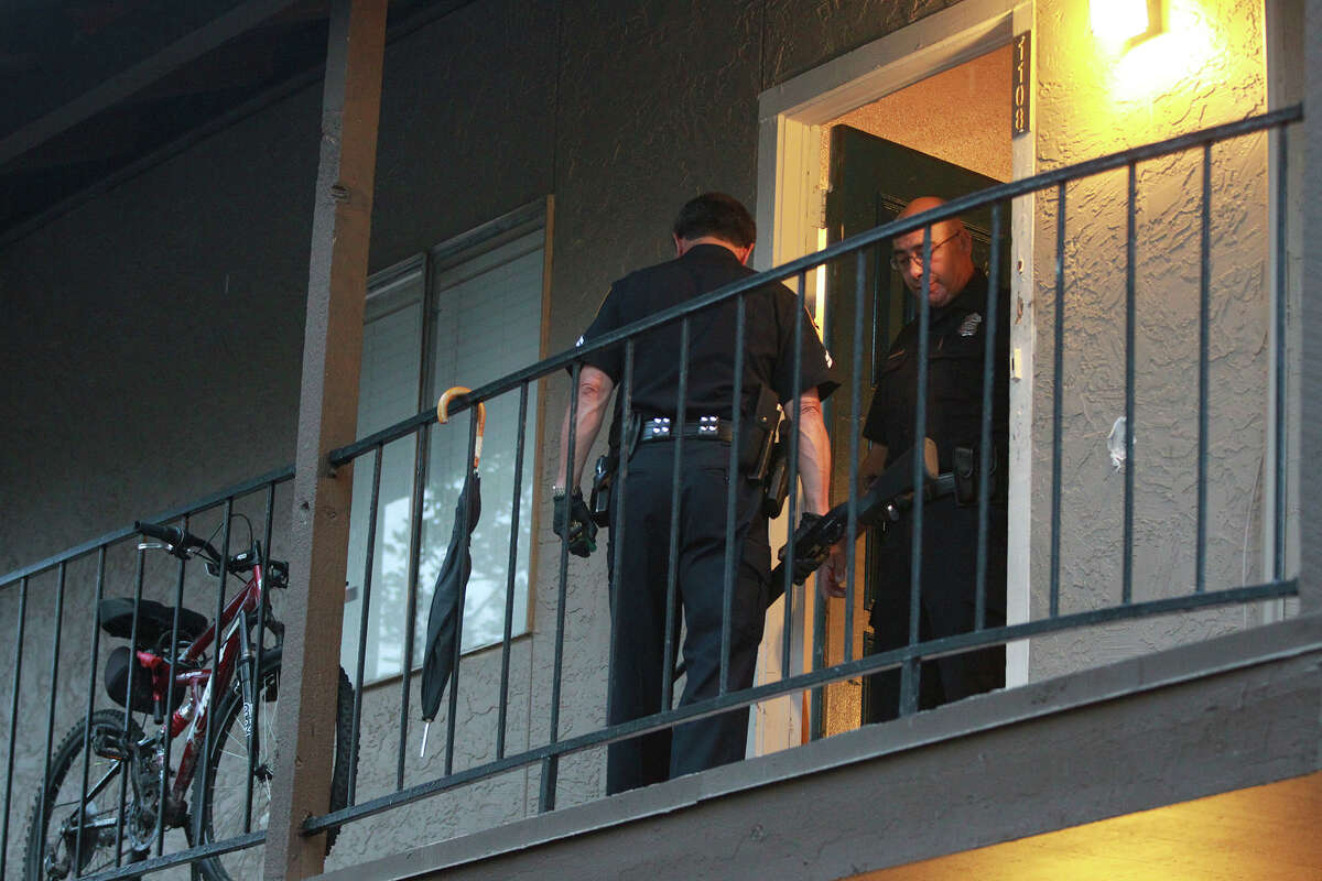 San Antonio police officer R.R. Sanchez (facing away) walks to a patrol car Wednesday June 25, 2014 with a shotgun at the Avistar at Chase Hill apartments on the 15,800 block of Chase Hill where two men were shot. One man died at the apartment and another died at University Hospital according to San Antonio police sergeant Andrew Ling.