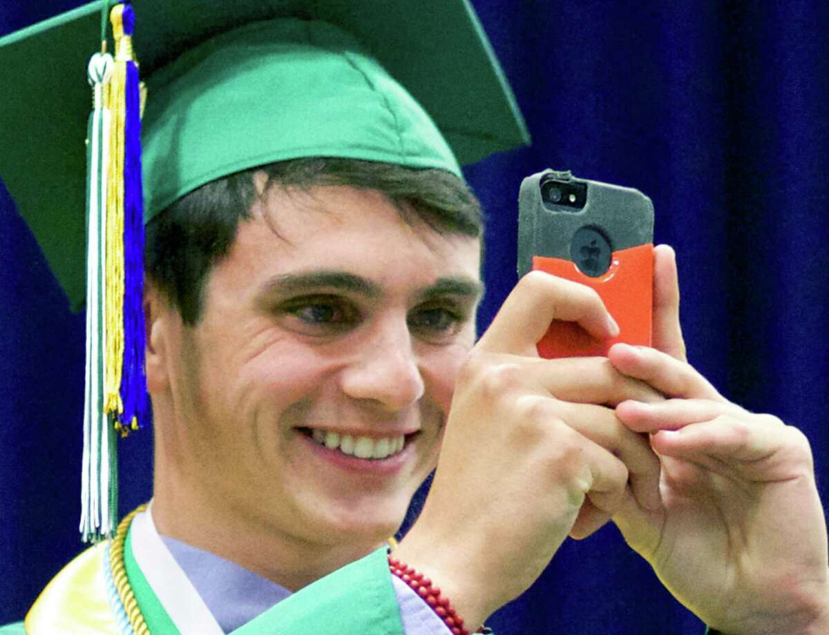 Nevan Swanson uses his iPhone to capture panoramic images of the scene before him before delivering his salutatory address during New Milford High School's June 21 commencement ceremony for the Class of 2014 at the O'Neill Center on the westside campus of Western Connecticut State University in Danbury.