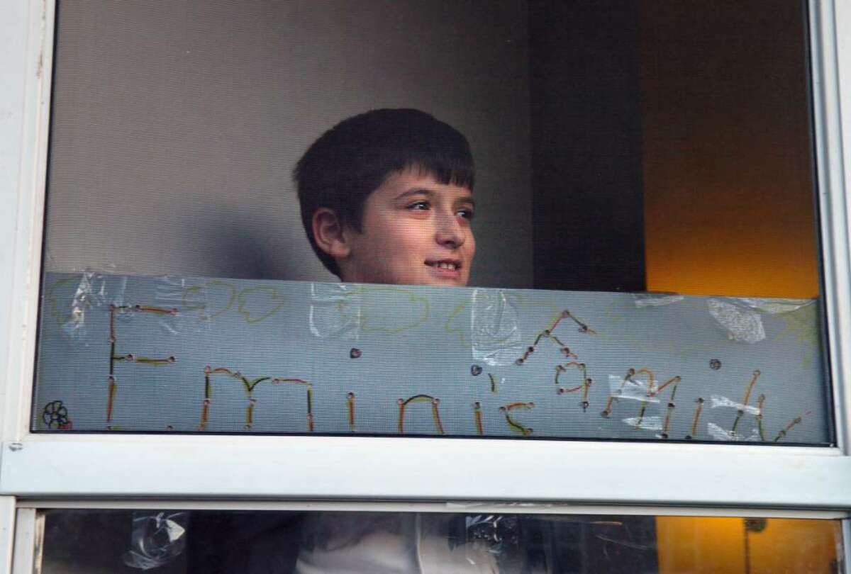 Eleven-year-old Dorart Emini looks out the front door of the home he shares with his sisters and his uncle Skender Emini in Naugatuck. Dorart made the sign on the front door three years ago when the Emini's first moved to Naugatuck. They have been living with their uncle in Naugatuck since their parents were murdered in Bridgeport in 2007. The children face having to return to their uncle's native Serbia if he cannot stay in the country.