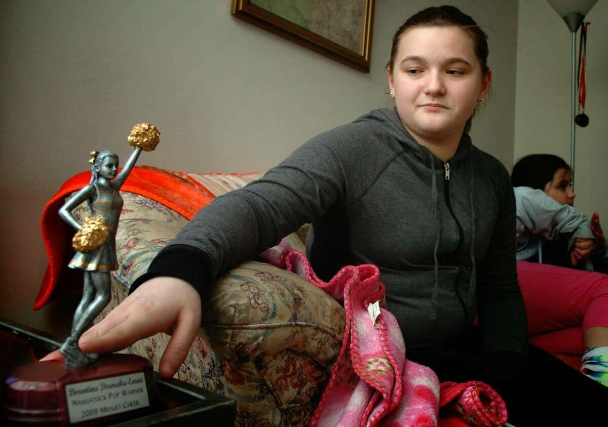 Thirteen-year-old Dorentina Emini touches the cheerleading trophy that her team won last year on the side table at her home in Naugatuck. Dorentina and her three siblings have been living with their uncle in Naugatuck since their parents were murdered in Bridgeport in 2007. The children face having to return to their uncle's native Serbia if he cannot stay in the country.