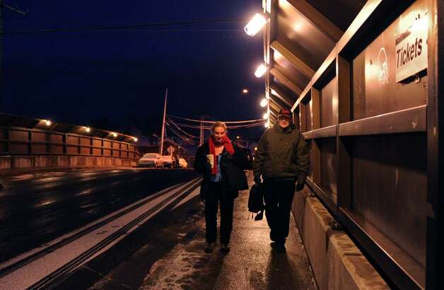 Amy Ficke and Gary Faulkner walk from the Fairfield Train Station to their cars parked on Round Hill Road.  The two met on the train four years ago and began walking together since neither could get a parking pass due to the long waiting list. Photo: Autumn Driscoll / Connecticut Post