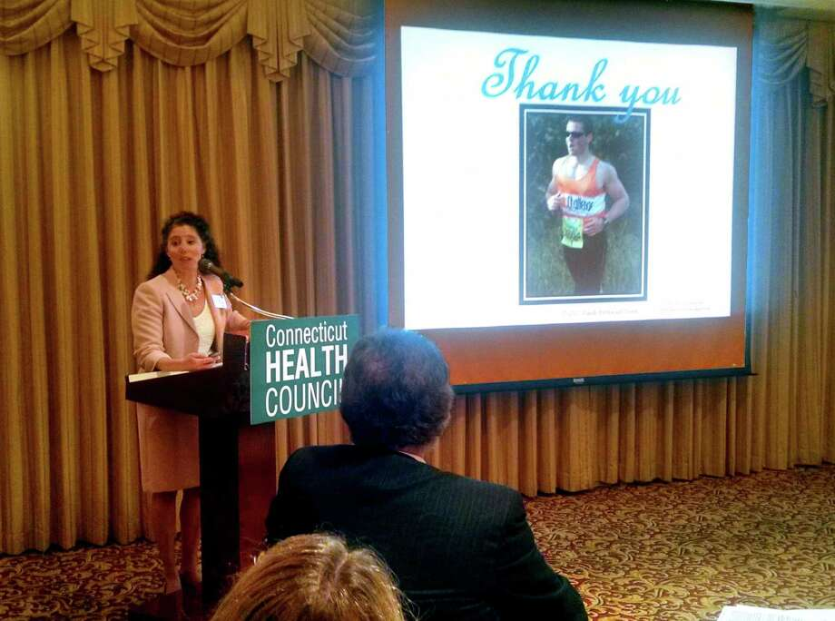"Fairfield resident and patient care reform advocate Randi Redmond Oster spoke Wednesday, June 25, 2014 at the Connecticut Health Council's ""The Patient is the Future"" event in Norwalk, Conn. To her right is a photo of her son Gary, now 20, who suffered from Crohn's disease in his teens. She wrote about the experience in her new book ""Questioning Protocol."" Photo: Amanda Cuda / Connecticut Post"