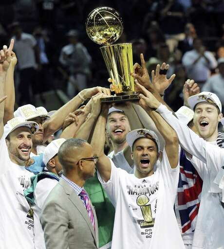 Tony Parker (center) and his teammates hold the Spurs' fifth Larry O'Brien Trophy up high on June 15. Photo: Edward A. Ornelas / San Antonio Express-News / © 2014 San Antonio Express-News