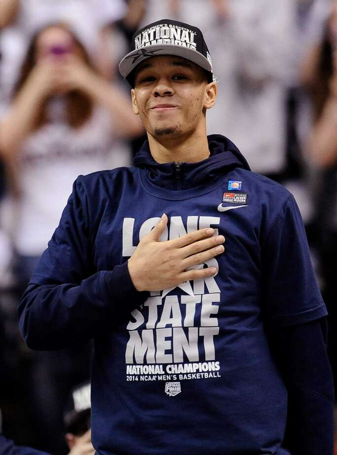 Connecticut's Shabazz Napier places his hand over his heart as he is cheered on by fans at a pep rally celebrating the program's fourth national championship, Tuesday, April 8, 2014, in Storrs, Conn. (AP Photo/Jessica Hill) Photo: Jessica Hill, AP