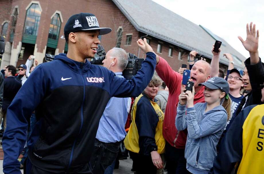 Connecticut's Shabazz Napier slaps hands with fans as he arrives with his team to a pep rally celebrating the program's fourth national championship, Tuesday, April 8, 2014, in Storrs, Conn. (AP Photo/Jessica Hill) Photo: Jessica Hill, Associated Press