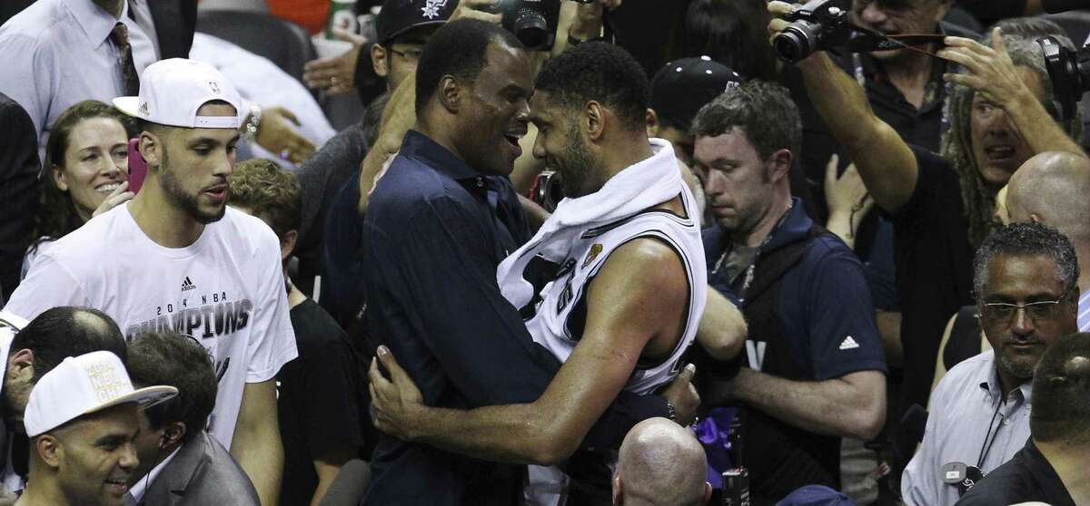 Tim Duncan shares a moment with his old teammate David Robinson after the Spurs wrapped up the franchise's fifth NBA championship against the Heat. They played on the Spurs' 1999 and 2003 title teams.