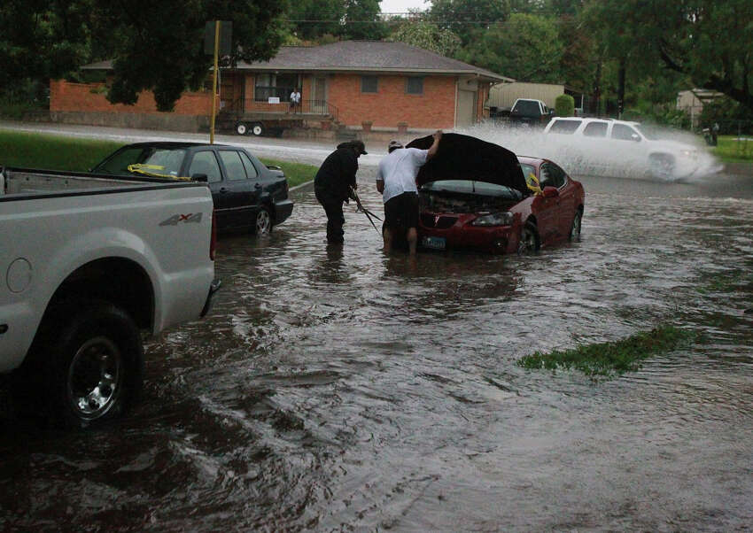 Raymond Martinez (center, white t-shirt) prepares to have his car towed Wednesday June 25, 2014 at Brightwood Place and N. New Braunfels after stalling in high water.