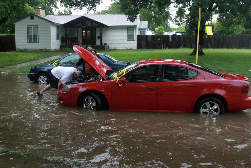 Raymond Martinez (under hood) prepares to have his car towed Wednesday June 25, 2014 at Brightwood Place and N. New Braunfels after stalling in high water.