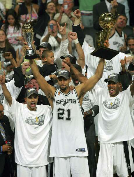 Spurs forward Tim Duncan raises both the Larry O'Brien Trophy for the Spurs' third NBA championship as well as his third NBA Finals MVP trophy after the Game 7 victory over the Pistons on June 23, 2005. Photo: Express-News File Photo / SAN ANTONIO EXPRESS-NEWS