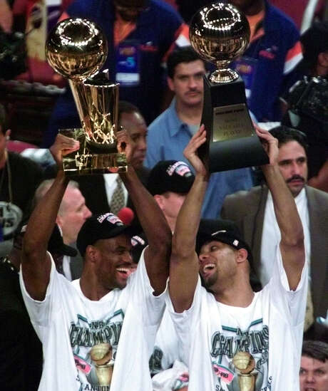 Center David Robinson (left) holds up the Spurs' first Larry O'Brien Trophy as NBA champions, while Tim Duncan, in just his second year in the NBA, holds the Finals MVP trophy after their Game 5 victory over the Knicks on June 25, 1999. Photo: Kin Man Hui / San Antonio Express-News / SAN ANTONIO EXPRESS NEWS