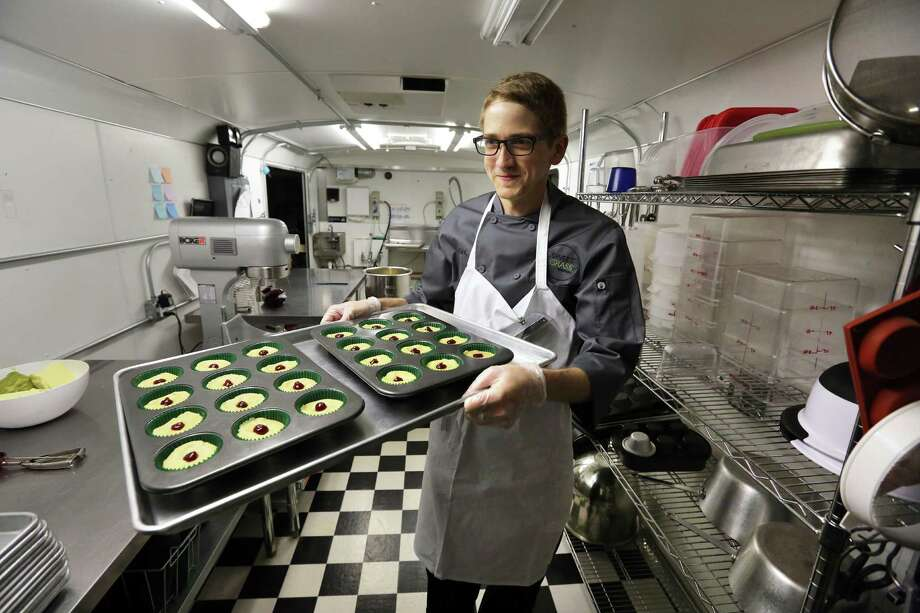 In this June 19, 2014 photo, chef Alex Tretter carries a tray of  cannabis-infused peanut butter and jelly cups to the oven for baking, at Sweet Grass Kitchen, a well-established gourmet marijuana edibles bakery which sells its confections to retail outlets, in Denver. Sweet Grass Kitchen, like other cannabis food producers in the state, is held to rigorous health inspection standards, and has received praise from inspectors, according to owner Julie Berliner. (AP Photo/Brennan Linsley)  ORG XMIT: MER2014062013571112 Photo: Brennan Linsley / AP
