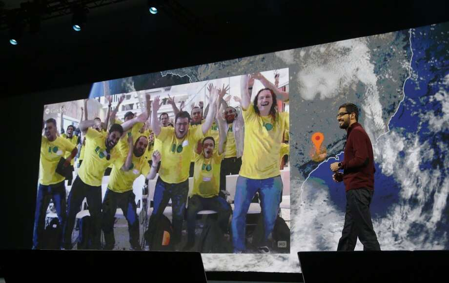 Sundar Pichai, senior vice president of Android, Chrome and Apps, right, smiles as a group watching live from Brazil is projected on the screen during the keynote presentation. Photo: Jeff Chiu, Associated Press