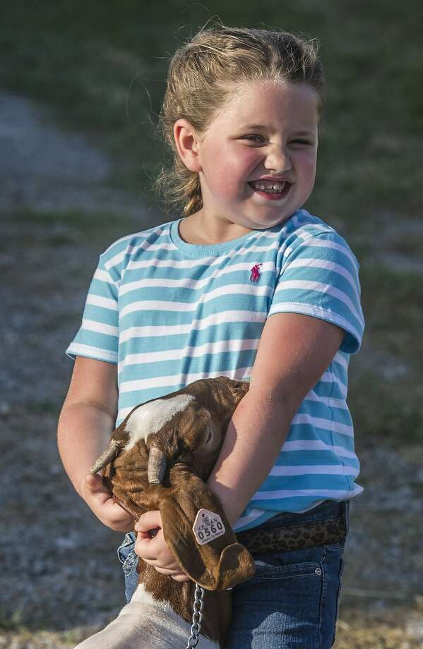If I win, can I eat the blue ribbon? Avery Turner hugs her entry before the goat show at the Garrard County Fair near Lancaster, 