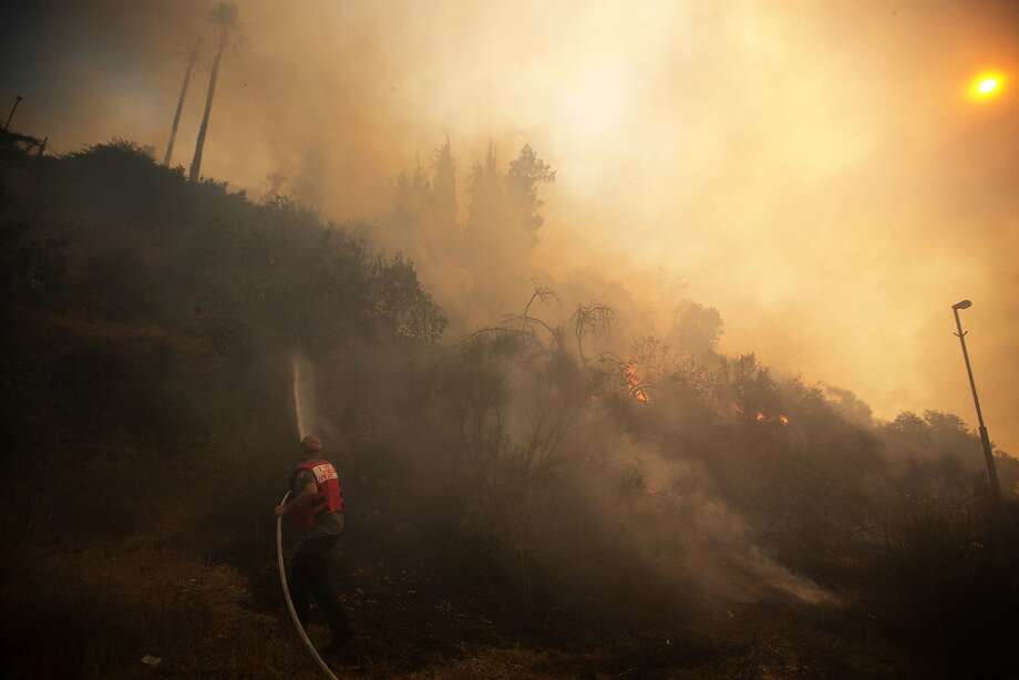 Brush burner: An Israeli firefighter battles a wildfire in the Jerusalem neighborhood of Ein Kerem. Hundreds of residents were evacuated before the blaze was contained. Photo: Menahem Kahana, AFP/Getty Images