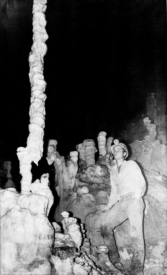 "Natural Bridge Caverns.  ""War Club"" is a strange offset stalegmite in the hall of the mountain kings.   Orion Knox Jr.   c.1962.   The individual in the picture is Reginald (Reggie) Wuest.  He was Mrs. Clara Wuest-Heidemann's son.  When Mrs. Heidemann passed away in 1997 he became President of Natural Bridge Caverns until his untimely death in 1998.  Today, his sons Brad Wuest, President, Travis Wuest, Vice President and his wife Joye Wuest, CFO, own and operate Natural Bridge Caverns.    As it turns out, the large offset formation in the photo was know as the Crankshaft but was broken some years ago, by a guest.  HOUCHRON CAPTION (07/27/2003):  Reginald Wuest, former president of the caverns, explores a cave in 1962. Photo: Orion Knox Jr., UNKNOWN / handout"