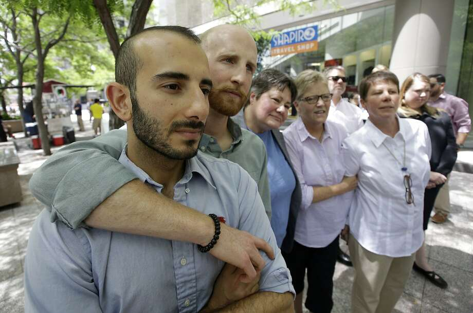 Five of the six plaintiffs who brought the lawsuit against Utah's gay marriage ban stand together at a news conference outside their lawyer's office in Salt Lake City after an appeals court struck down the ban. Photo: Rick Bowmer, Associated Press