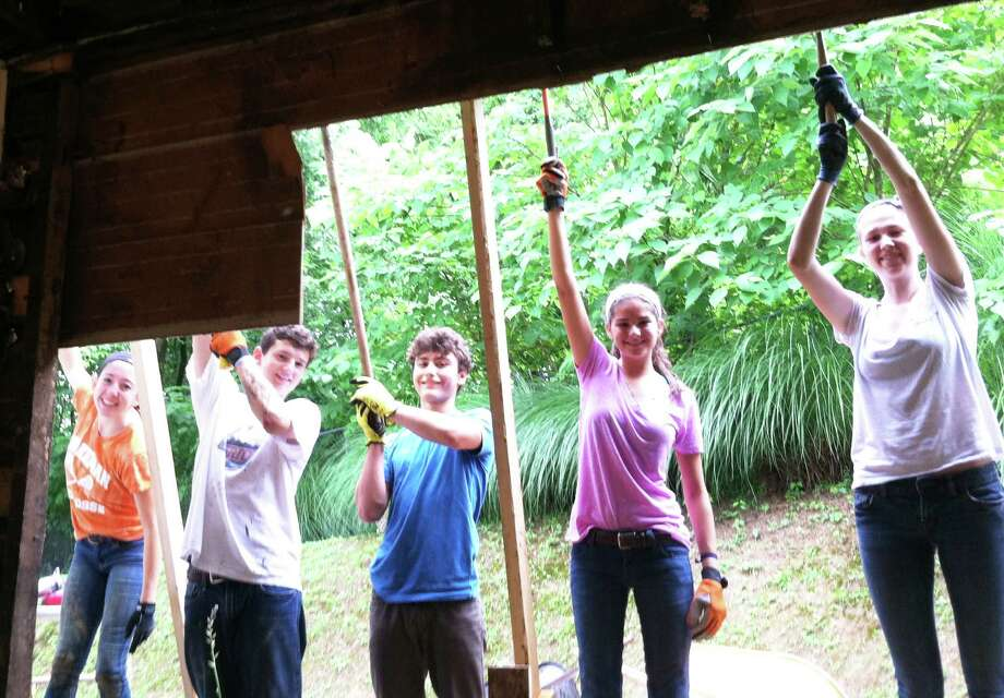 A work crew from Fairfield holds up a gutter being installed on a house in Apalachia last summer. From left: Claire Burns, Matt Stern, Jacob Russell, Emma DesGranges, and Lily McGonagle. Kids involved in this year's project will leave Fairfield on June 28. Photo: Contributed Photo / Fairfield Citizen
