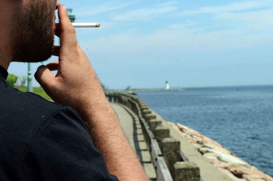 A man smokes a cigarette Wednesday, June 25, 2014, while enjoying the view St. Mary's-by-the-Sea in Bridgeport, Conn. Photo: Autumn Driscoll / Connecticut Post
