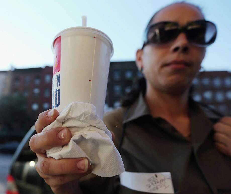 "A woman displays a 21-ounce soda, a size banned by the New York City Board of Health in 2012. The City Council should get on board with Metro Health's ""drink responsibly"" campaign. Photo: Mario Tama / Getty Images / 2012 Getty Images"