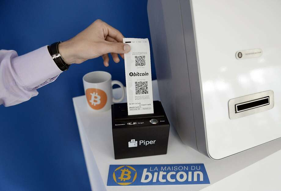 A man takes a receipt from a vending machine that dispenses bitcoins at La Maison du Bitcoin in Paris. Photo: Stephane De Sakutin, AFP/Getty Images
