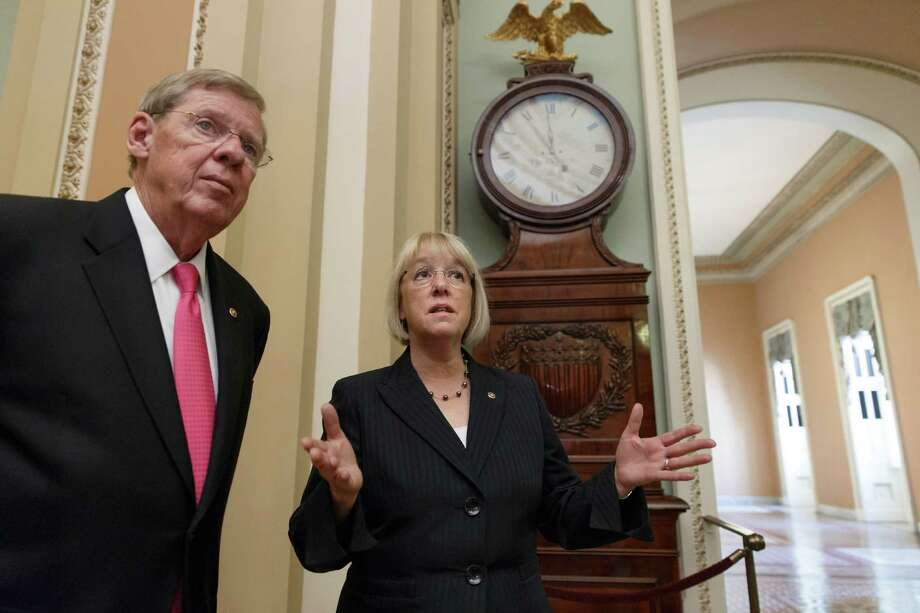 Sen. Johnny Isakson, R-Ga., left, and Sen. Patty Murray, D-Wash., meet before walking into the Senate chamber to shepherd the Workforce Innovation and Opportunity Act which aims to help job seekers gain valuable employment skills, at the Capitol in Washington, Wednesday, June 25, 2014. Sen. Isakson, a Republican, and Sen. Murray, a Democrat, praised the bipartisan effort on both sides of the Hill which would eliminate excess federal programs and overhaul requirements throughout the job training system.  (AP Photo/J. Scott Applewhite) Photo: J. Scott Applewhite, STF / AP