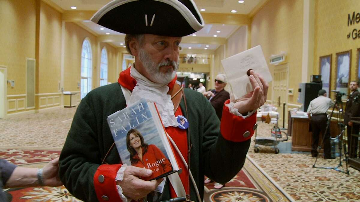 """A man explains to filmmakers Carl Deal and Tia Lessin how he?•s claimed Sarah Palin as ?'his woman?"""" and has an invitation for her, sealed with a ?'T?"""" for tea party, while wearing a costume that very clearly states ?'I have a valid political point to make and should be taken quite seriously?"""" in a scene from CITIZEN KOCH."""