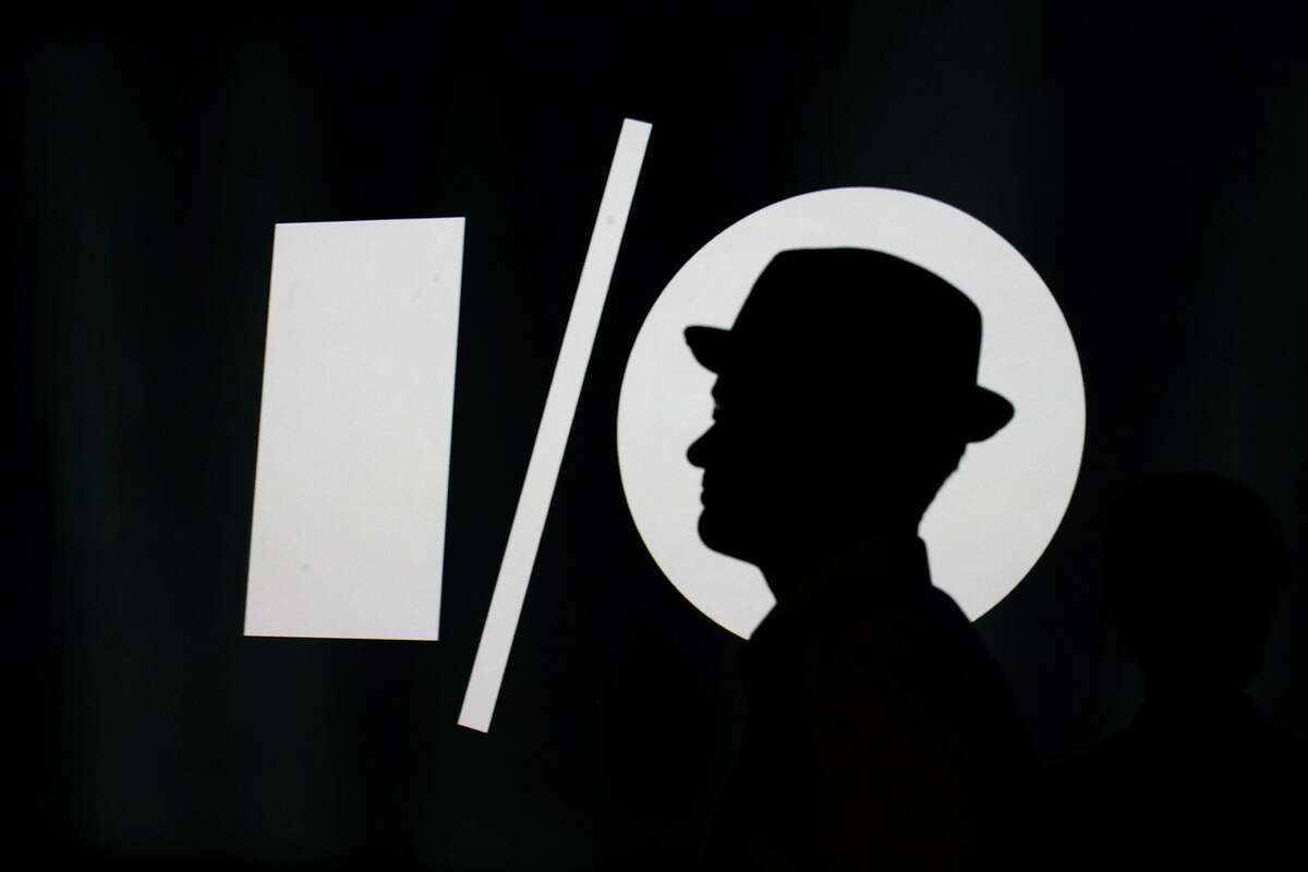 A man passes the Google I/O logo before the keynote speech at the Moscone Center in San Francisco, Calif. on Wednesday, June 215, 2014. Google unveiled new products geared towards the home, automobiles and wearables at their annual I/O conference.