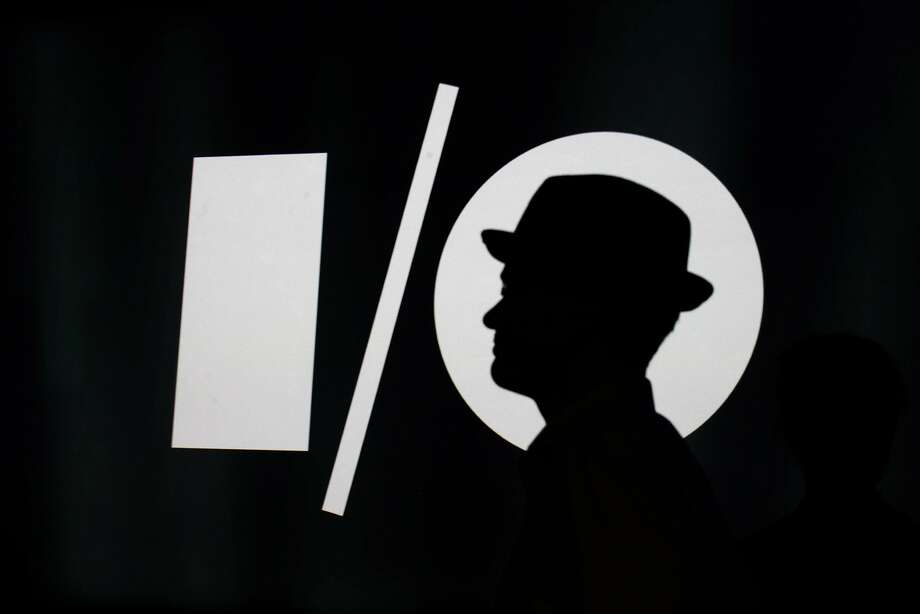 A man passes the Google I/O logo at the conference. Photo: James Tensuan, The Chronicle