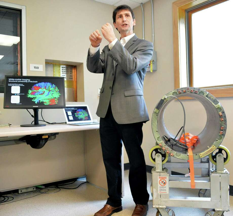 Luca Marinelli, MRI lab manager at GE Global Research, stands next to a gradient coil prototype, dedicated MRI brain scanner, right, as he addresses a tour group at GE Global Research Wednesday, June 25, 2014, in Niskayuna, N.Y.  (John Carl D'Annibale / Times Union) Photo: John Carl D'Annibale / 00027445A
