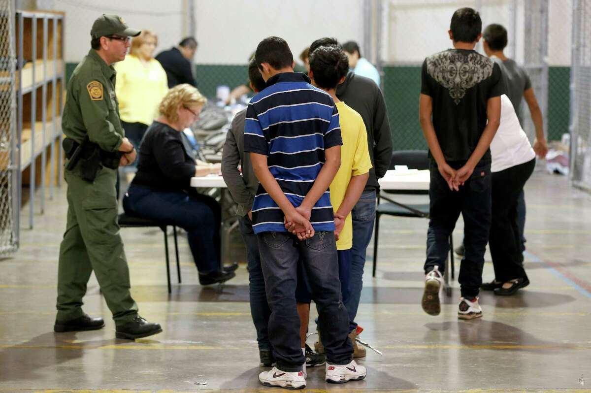 NOGALES, AZ - JUNE 18: Boys wait in line to make a phone call as they are joined by hundreds of mostly Central American immigrant children that are being processed and held at the U.S. Customs and Border Protection Nogales Placement Center on June 18, 2014, in Nogales, Arizona. Brownsville, Texas, and Nogales, have been central to processing the more than 47,000 unaccompanied children who have entered the country illegally since Oct. 1. (Photo by Ross D. Franklin-Pool/Getty Images)