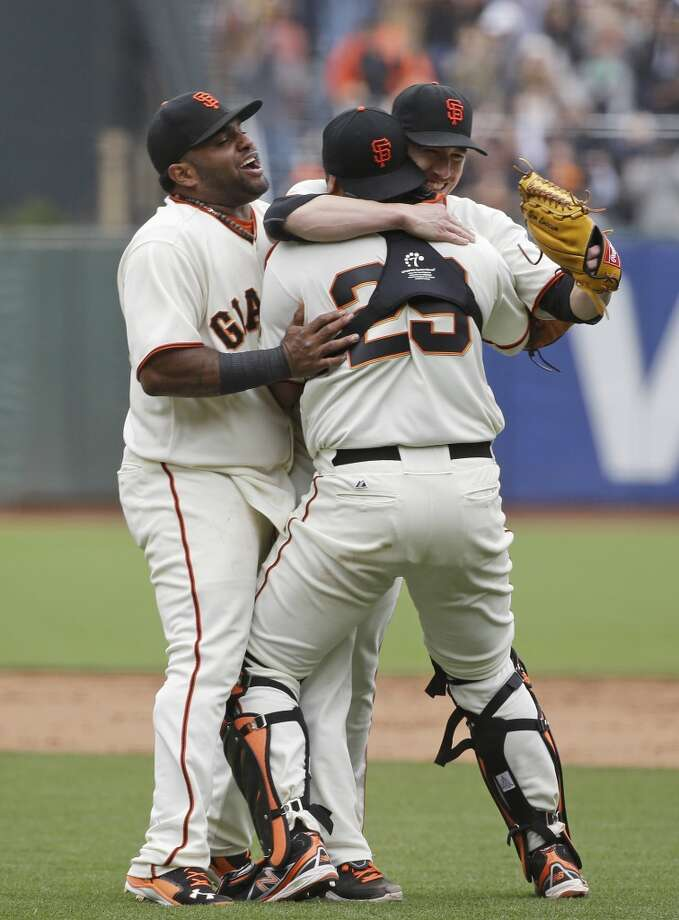 San Francisco Giants pitcher Tim Lincecum is embraced by catcher Hector Sanchez as third baseman Pablo Sandoval joins in. Photo: Eric Risberg, Associated Press