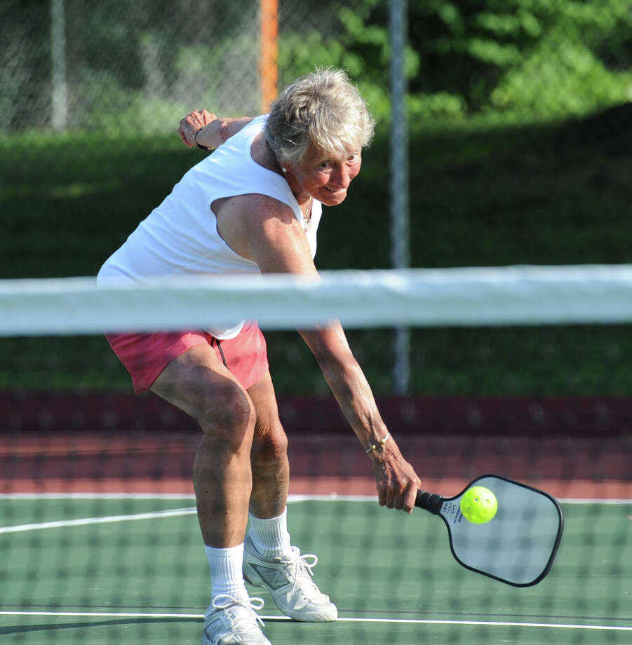 Dee Woods, of Old Greenwich, who said she was in her 70s, plays pickleball during the Town of Greenwich Parks & Recreation Department ceremony for the re-opening of the resurfaced Christiano tennis courts that were also lined for the new racket sport known as pickleball, at the courts in the Chickahominy section of Greenwich, Conn., Wednesday, June 25, 2014. Pickleball consists of two to four players using light-weight solid paddles to hit a plastic ball over a net. Woods was one of the players involved in the demonstration of pickleball that was put as part of the ceremony. Photo: Bob Luckey / Greenwich Time