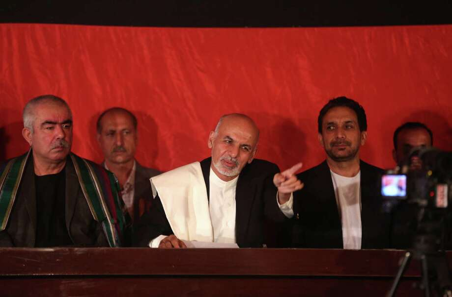 Afghanistan's presidential candidate Ashraf Ghani Ahmadzai, center, asks a cameraman to move to the right side, during an event at his residence in Kabul, Afghanistan, Wednesday, June 25, 2014. Ashraf Ghani Ahmadzai, called on Abdullah to rejoin the process and demanded that the commission stick to the official timetable for releasing preliminary results next week. (AP Photo/Massoud Hossaini) Photo: Massoud Hossaini, STF / AP